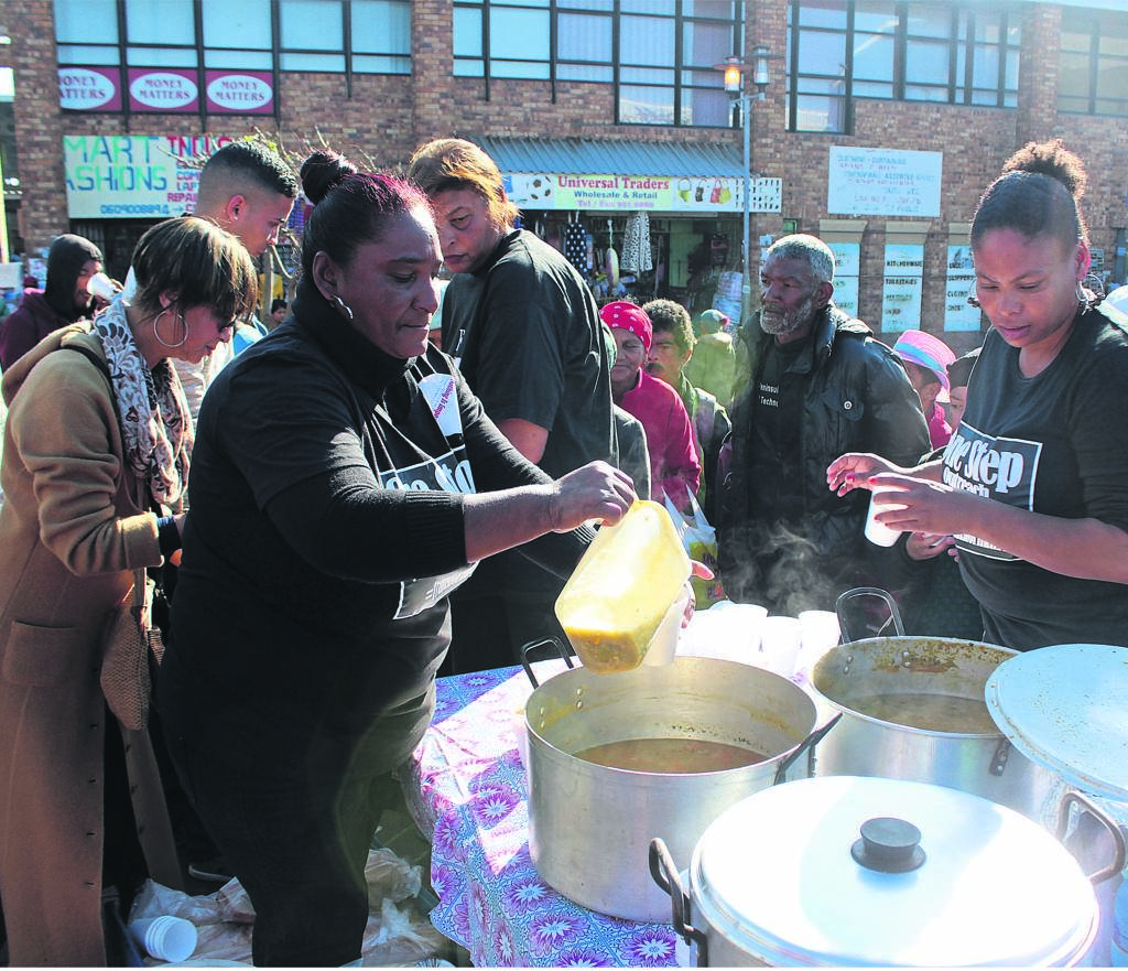Members of the organisation serving soup for the hungry attendees.