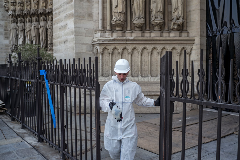 A construction worker walks through a gate at the Notre-Dame de Paris Cathedral during preliminary work in Paris. (Rafael Yaghobzadeh, Pool, AFP)