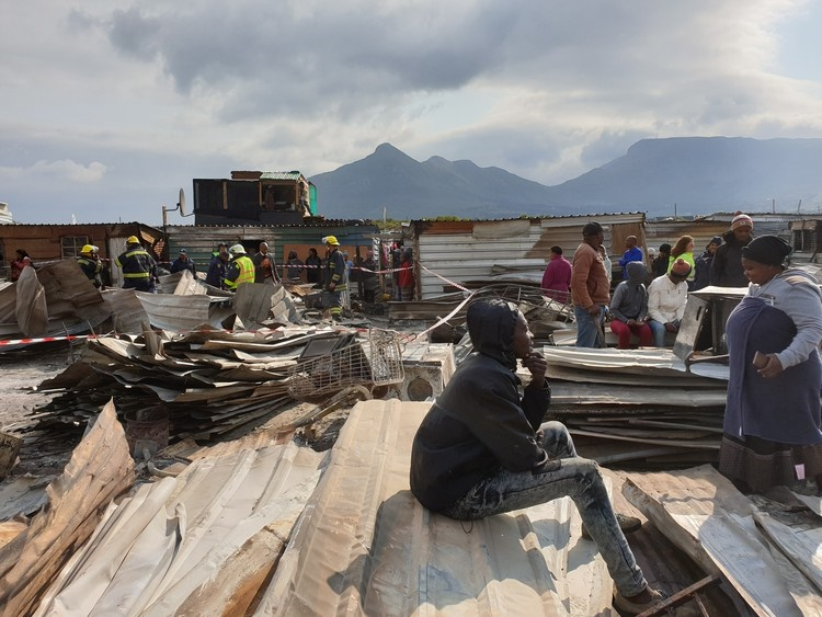 A young man sits on corrugated iron sheeting and stares ahead. A fire tore through Masiphumelele on Monday morning. (Mary-Anne Gontsana, GroundUp)