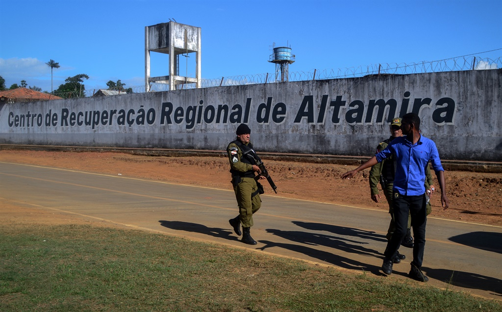A police officer patrols the surroundings of the Altamira Regional Recovery Centre after at least 57 inmates were killed in a prison riot, in the Brazilian northern city of Altamira, Para State. (Bruno Santos, AFP)