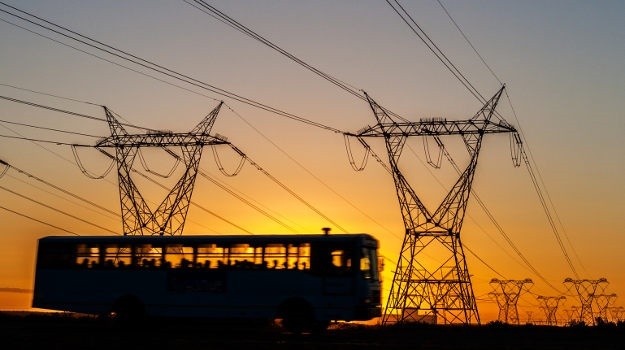 A bus passes power lines at dusk. (iStock)
