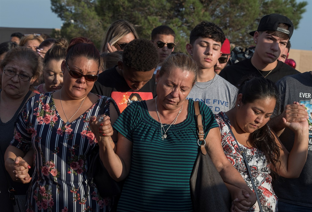 People pray at a makeshift memorial for victims of Walmart shooting that left a total of 22 people dead at the Cielo Vista Mall WalMart in El Paso, Texas. (Mark Ralston, AFP)