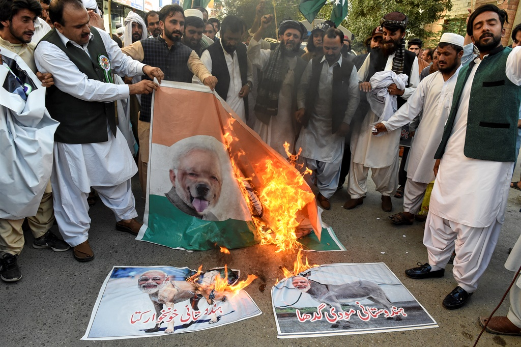 Protesters burn posters featuring images of Indian Prime Minister Narendra Modi during a protest in Quetta, a day after India stripped the disputed Kashmir region of its special autonomy. (AFP)