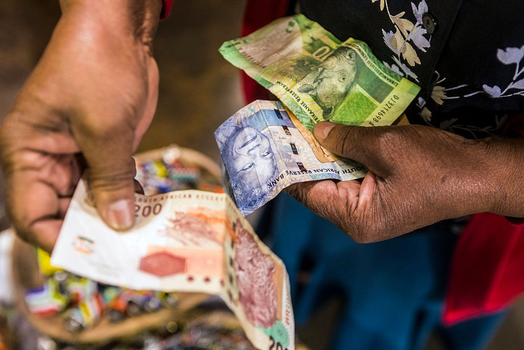 A vendor counts out rand banknotes while working i