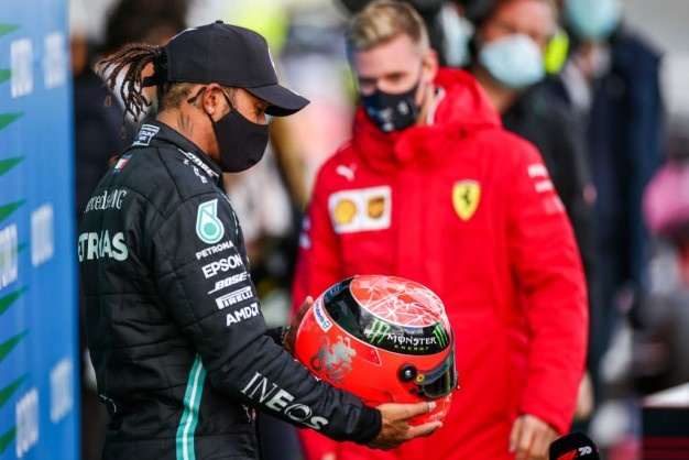 Mick Schumacher presents Lewis Hamilton with his father Michael Schumacher's helmet to celebrate equalling his father's achievement of 91 wins during the F1 Eifel Grand Prix at Nuerburgring. Image: Peter Fox/Getty.