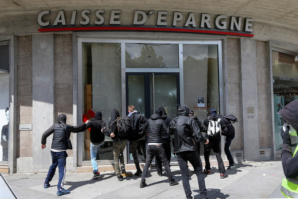 "Protesters dressed in black try to break a bank window on the sides of a rally called by the ""Gilets Jaunes"" (Yellow Vests) movement. (Francois Nascimbeni, AFP)"