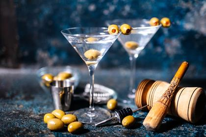 Martini cocktail drink with olives garnish and too