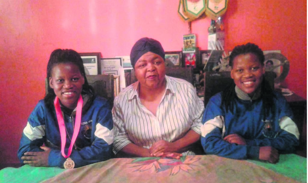 Banyana Banyana player Noxolo Cesane wearing her 2019 Cosafa medal. She is with her granny Nompumelelo Mayekiso and her twin sister Sinoxolo Cesane. Both Noxolo and Sinoxolo play for the University of the Western Cape FC.