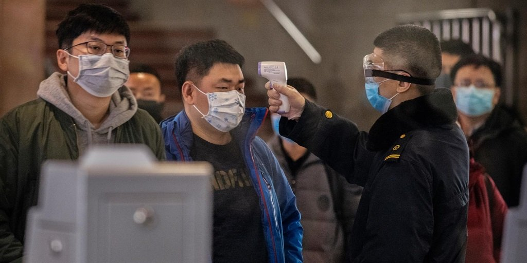 Passengers who just arrived on a train from Wuhan, China are screened for coronavirus in Beijing.