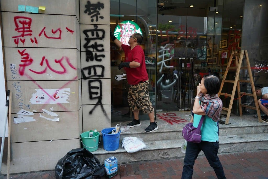 A man cleans up graffiti put up by protesters on the front of a Starbucks coffee shop in Hong Kong. (September 30, 2019) (Jerome Taylor/AFP)