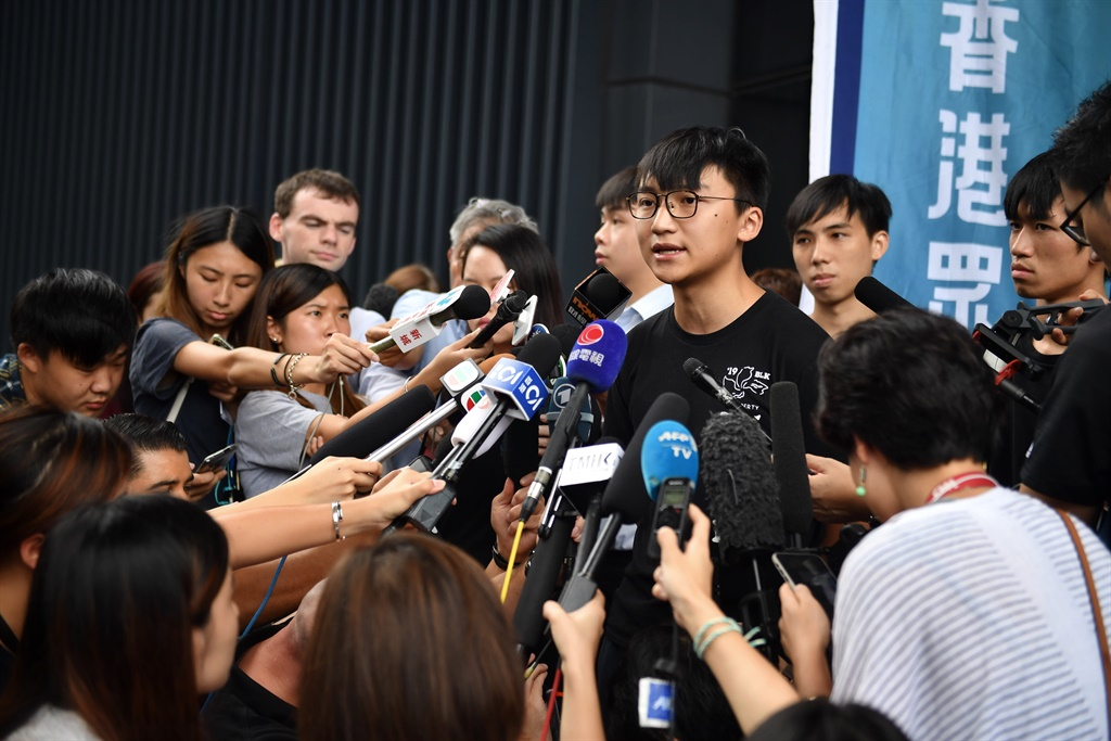 Demosisto vice chairperson Isaac Cheng speaks to members of the press on the arrest of party leaders Joshua Wong and Agnes Chow, in Hong Kong. (Lillian Suwanrumpha, AFP)