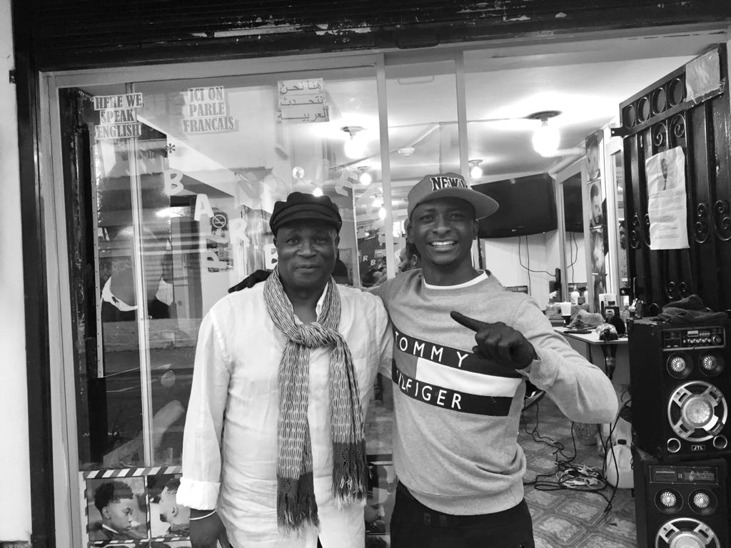 Ahmed Sanoussi (right) standing outside of his hair salon with the Congolese-French documentary filmmaker, David-Pierre Fila. (Julian Cola)