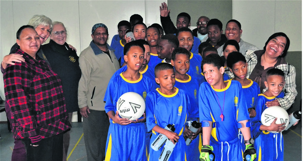 Rotarians and learners with disabilities celebrate the donation of their new soccer kit.