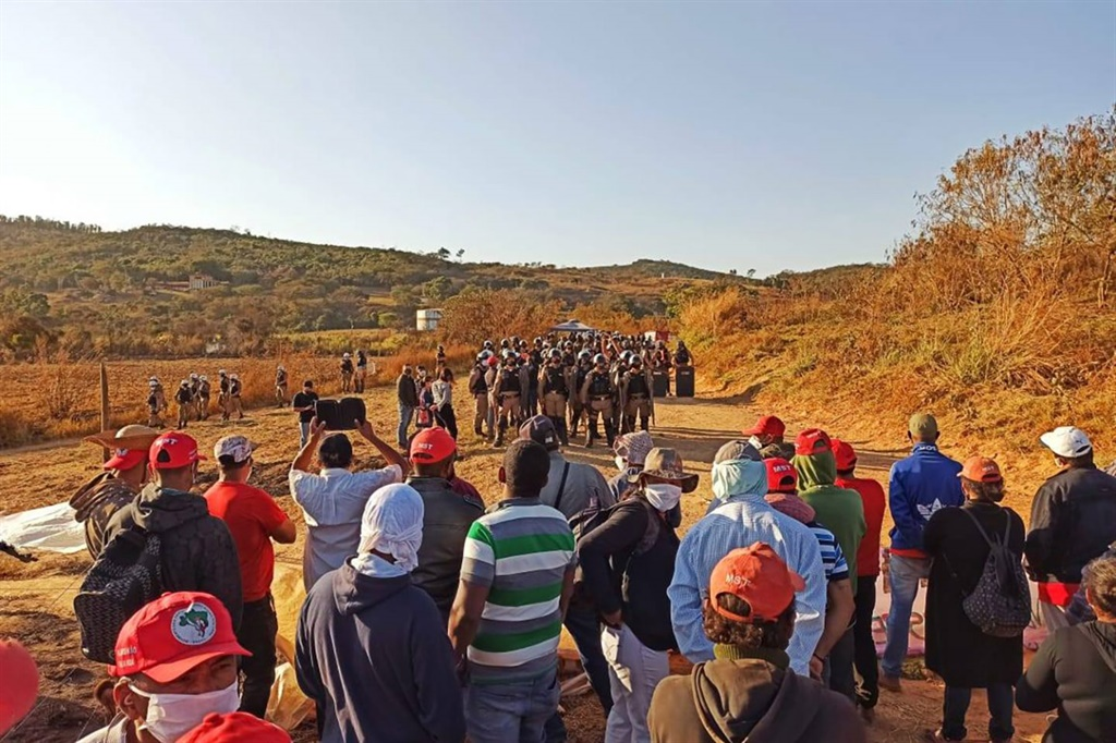Members of the Landless Rural Workers' Movement (MST) face a police line while protesting against evictions that took place at the Quilombo Campo Grande camp in Brazil. (Photograph supplied by MST)