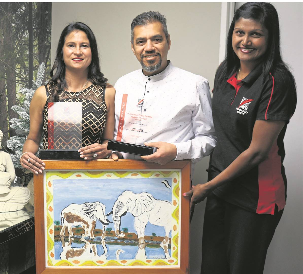 From left: Dr Darshanee Patel (Medical Aesthetics) and husband Dr Sanjay Maharaj (Cardiologist) receive their Red Feather Legacy Certificates and a painting donated by artist Reggie Gopaul to the Community Chest, from Angie Narayanan.PHOTO: supplied