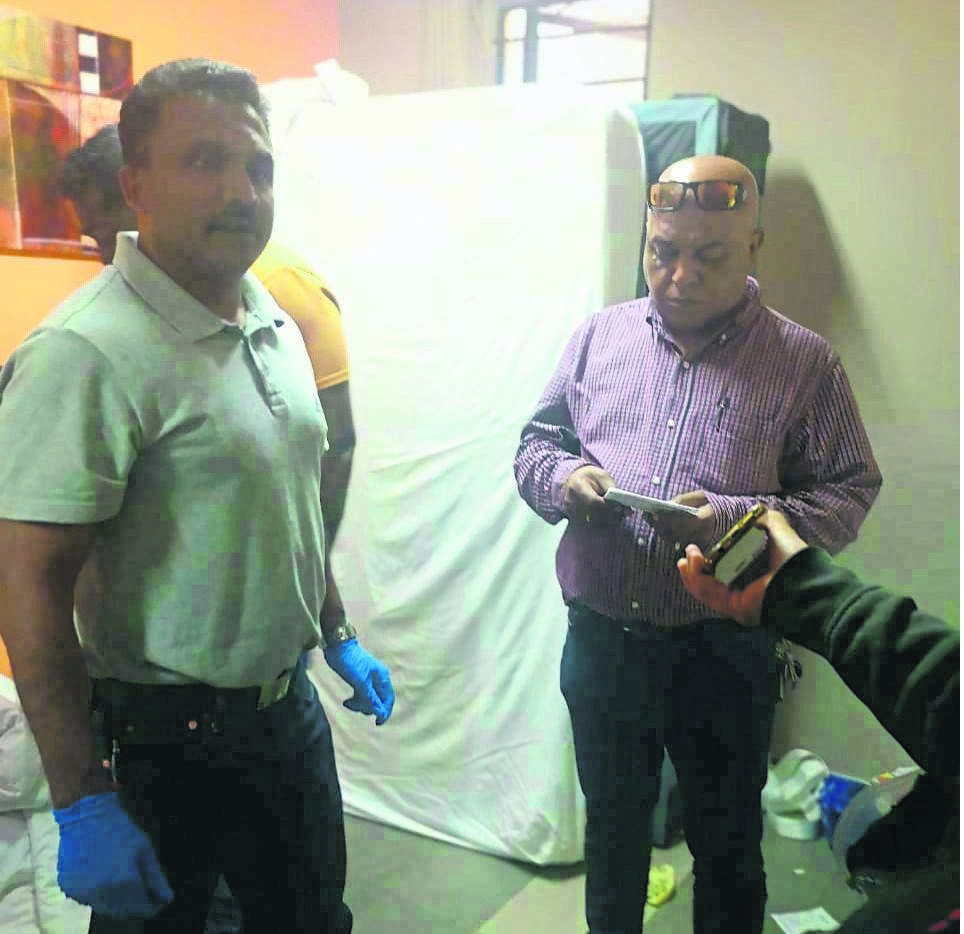 Pietermaritzburg crime intelligence officer Captain Rumen Maistry (left) and Alexandra Road Detective R. Naidoo sweep the room Roland Pillay was staying in and where he hanged himself yesterday morning.