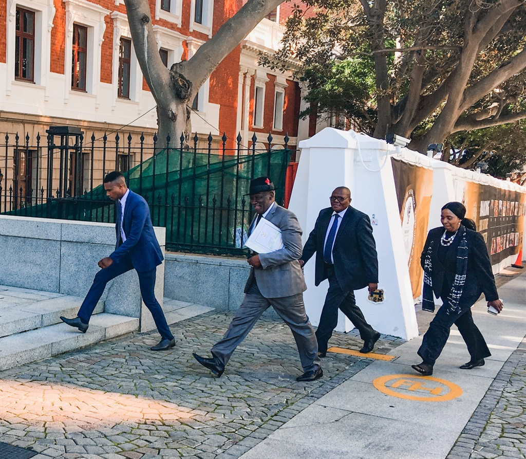 Police Minister Bheki Cele (second from the left, with hat) on his way to answer questions in the National Assembly on Wednesday. (Jan Gerber/News24)
