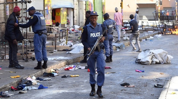 A police officer walks through the Johannesburg city centre on September 2 after shops, mainly foreign run, were set alight and looted. (Felix Dlangamandla, Netwerk24)