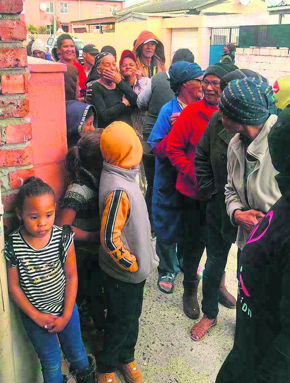 Eastridge residents standing outside the house of non-profit organisation, We Desire To Inspire, to collect food.