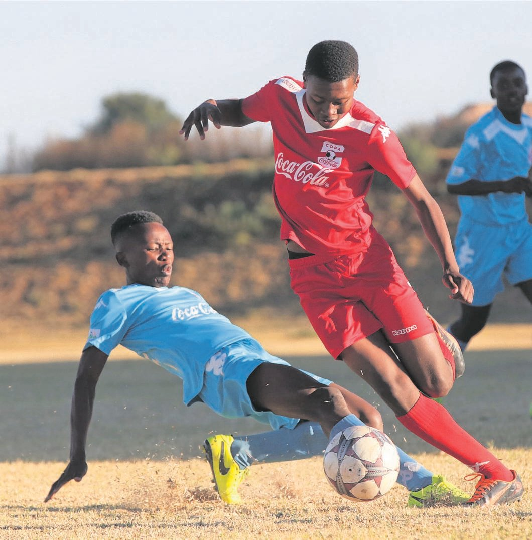 Andile Mofolo of the Dr Reginald Cingo Comprehensive School tackles Neo Metsing of the Samuel Johnson School in the provincial final of the Coca-Cola Schools Championship in Welkom on 30 August.