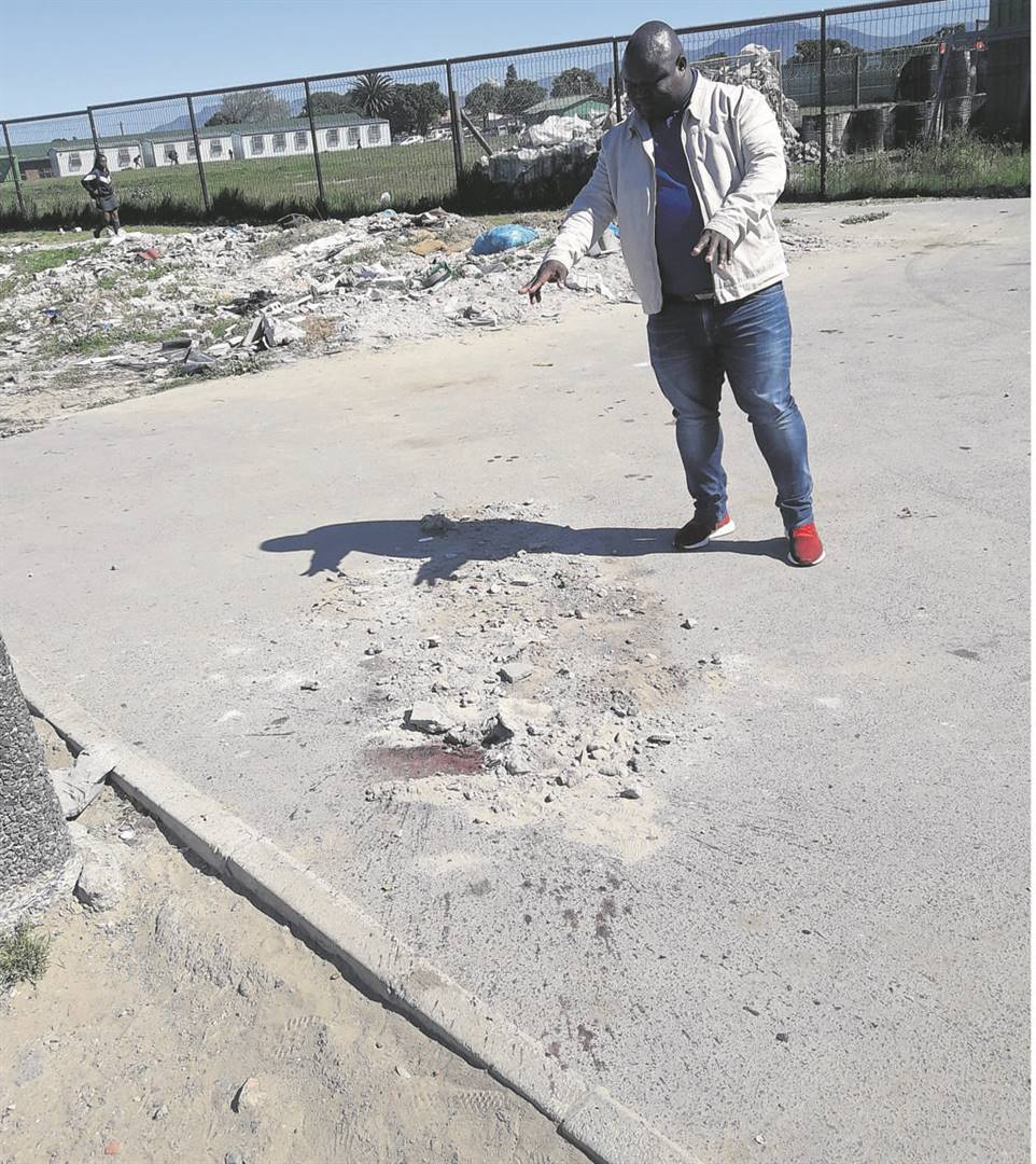 Councillor Bongani Ngcombolo is pointing at the blood stains where a body of a woman was found. The stains were covered with sand. PHOTO: UNATHI OBOSE
