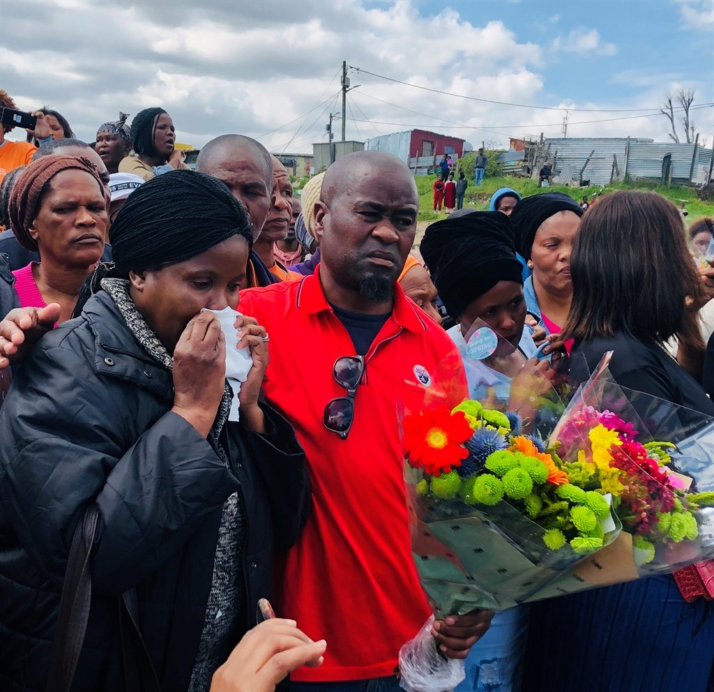 The mother of a 24-year-old woman who was found dead next to a rubble-strewn at the end of a cul-de-suc in Gugulethu is comforted by her brother. (Kamva Somdyala, News24)
