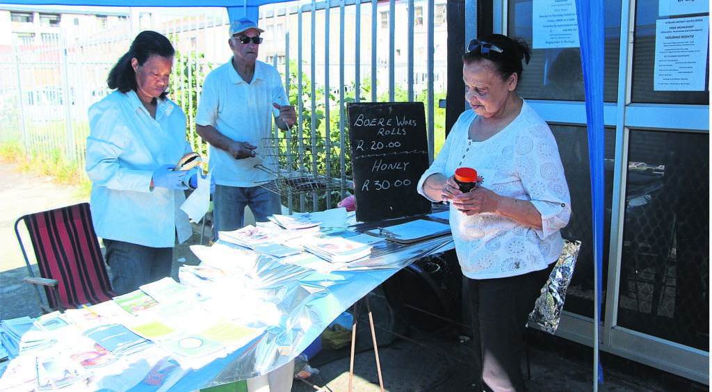 The open day was also held to raise funds for the NGO. Boerewors rolls and honey were sold to attendees and people passing by. From left are Cecilia Alcock, Keith Manter (members of the centre) and local resident Yvonne Mocke. PHOTO: SIPHESIHLE NOTWABAZA