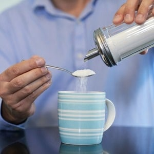 Close Up Of Mature Man Adding Sugar To Hot Drink A