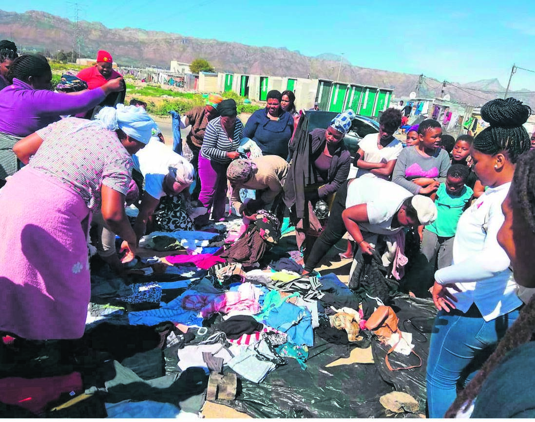 Residents of Ezinkomeni informal settlement in Nomzamo helping themselves to donated clothes on Saturday 14 September.