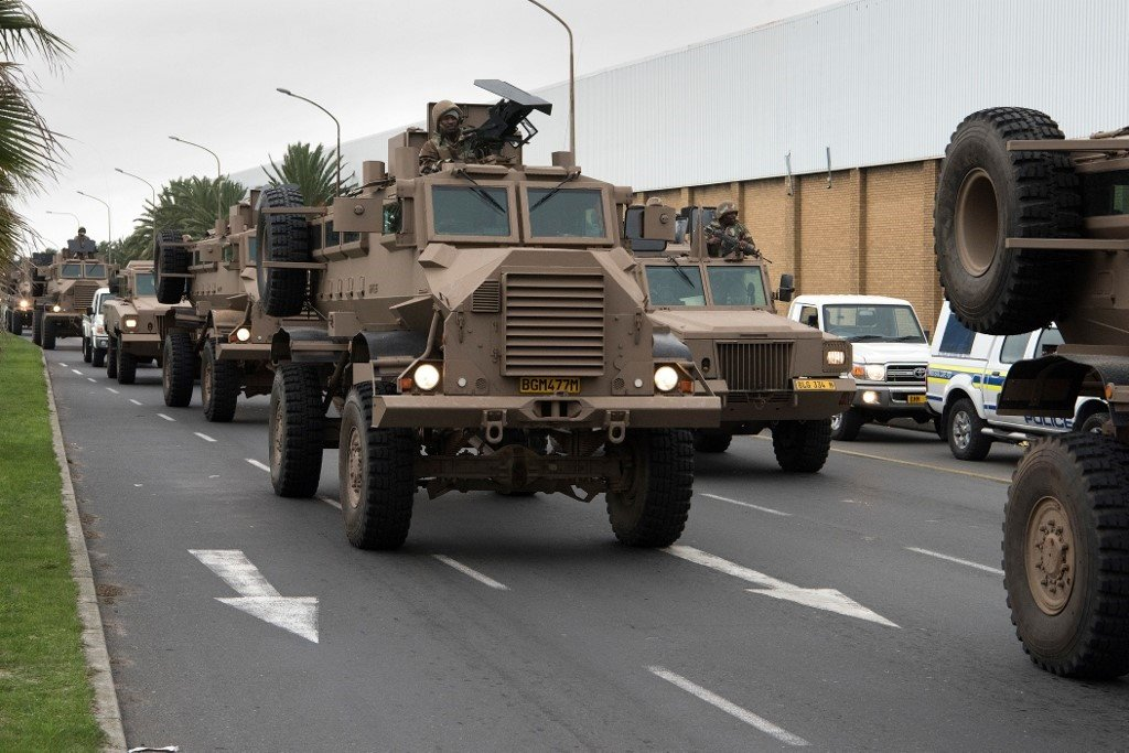 A convoy of South African National Defense Force (SANDF) drives through a street close to Manenberg, Cape Town. (Rodger Bosch/AFP).