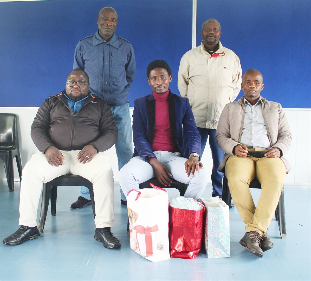 photo: suppliedTeachers from Sisekelo High School (front row, from left) principal Mr NO Khanyile, Bayanda Zungu(out-going teacher) with his farewell presents, (back fron left)Mr SM Magubane Mc of the day, and school governing body members (back row from left) Mr Mhlongo and Mr Mkhize.