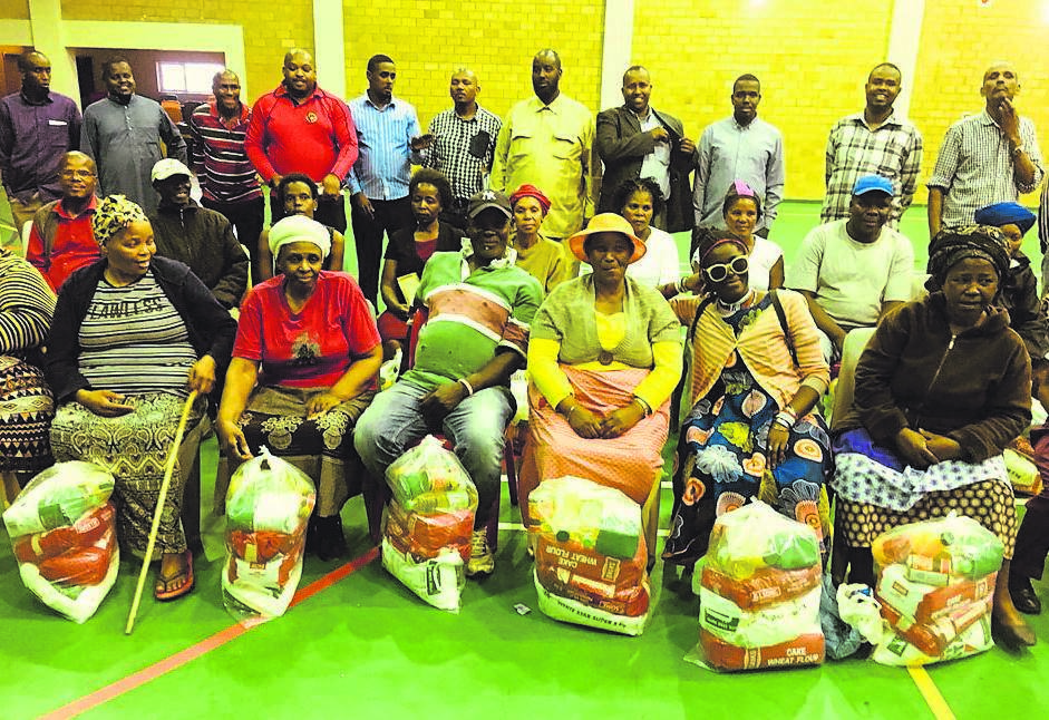 Ward 85 councillor Simthembile Mfecane surrounded by Somali nationals and beneficiaries of the food donated by the Somali community on Thursday 12 September at Nomzamo Community Hall.