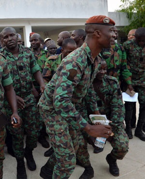 A delegation of mutinous soldiers reacts after taking part in negotiations with Ivory Coast's defence minister (unseen) in Bouake. (AFP)