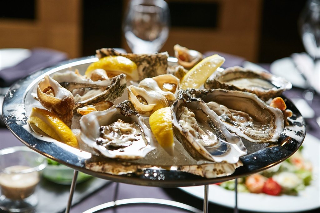 A platter of fresh organic raw oysters on ice at r