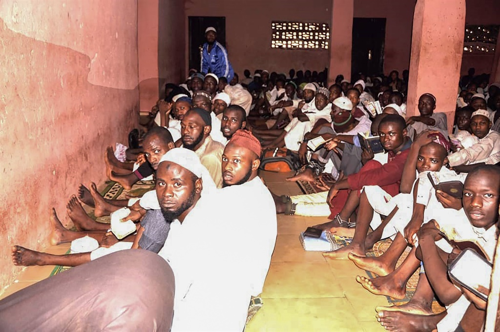 """Some of the 300 male students of """"different nationalities"""" sit on the floor in chains outside a torture chamber in the Rigasa area of Kaduna in northern Nigeria after being rescued by police from an Islamic seminary where they were tortured and sodomised. (AFP)"""