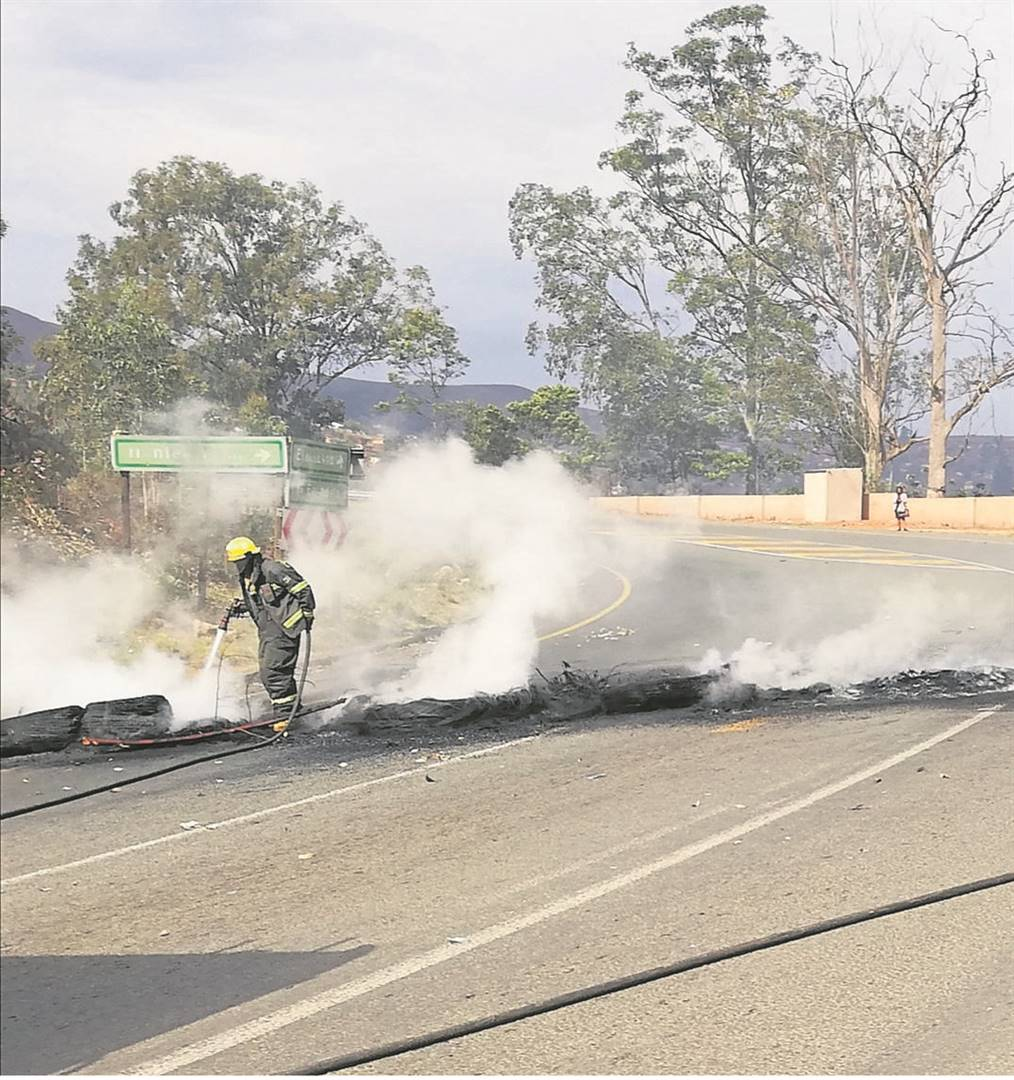 PHOTO: lethiwe makhanyaFire fighters putting out a fire caused by protesters burning tyres on Monday at Henley.