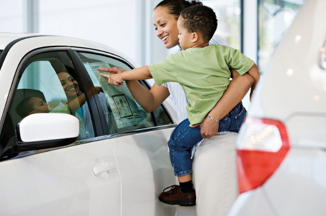 A woman and her child browsing through a car dealership.