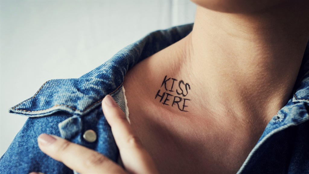 """Shot of an unidentifiable young woman revealing a written message reading """"kiss here"""" on her neck"""