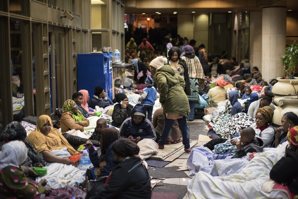 Dozens of people camp in a corridor close to the offices of the United Nations High Commission for Refugees in Cape Town, demanding to be removed from South Africa saying they were no longer safe. (Rodger Bosch, AFP)