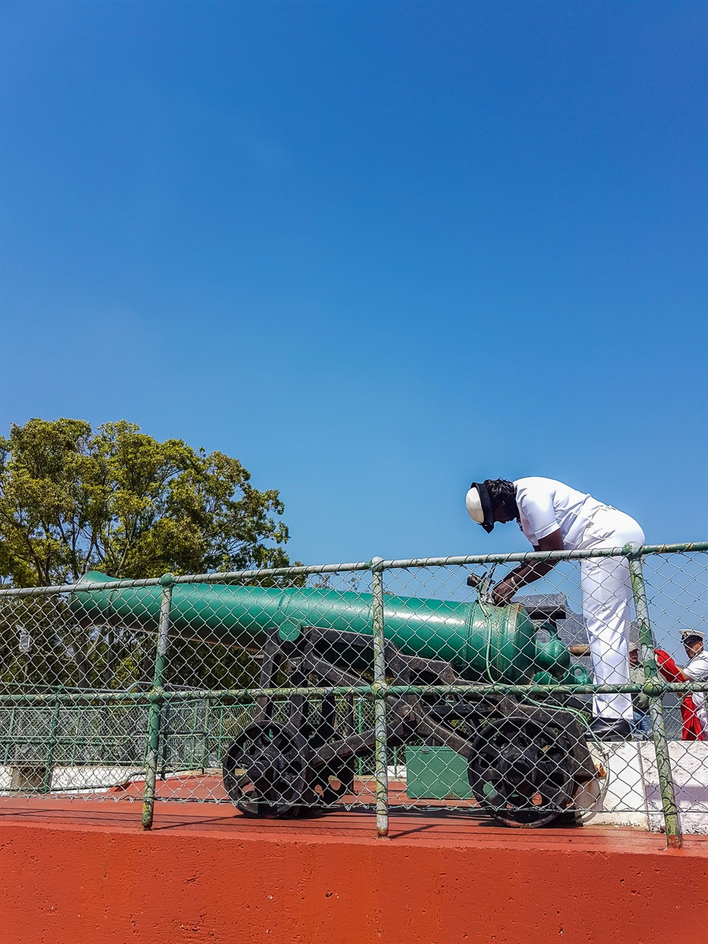 navy officer attending to the noon gun cannon in c