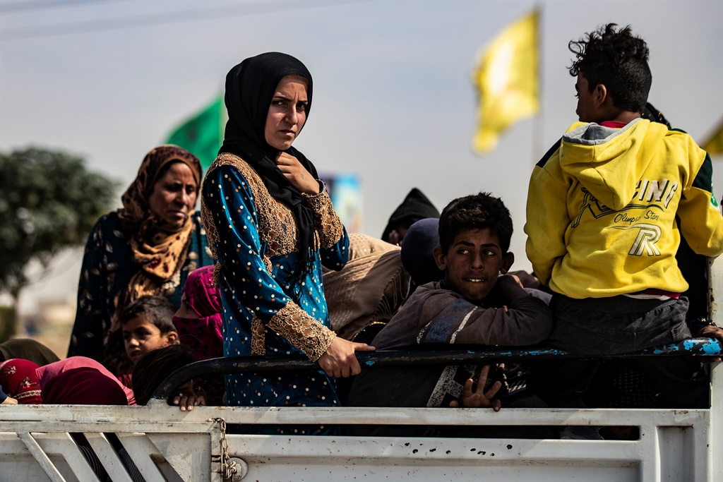 Displaced Syrians sit in the back of a pick up truck as Arab and Kurdish civilians flee amid Turkey's military assault on Kurdish-controlled areas in northeastern Syria. (Delil Souleiman, AFP)