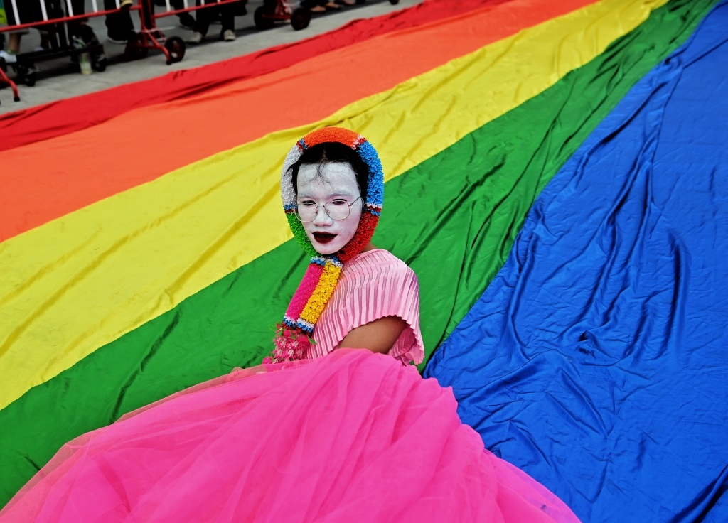 An LGBTQ activist lies on a large rainbow banner.