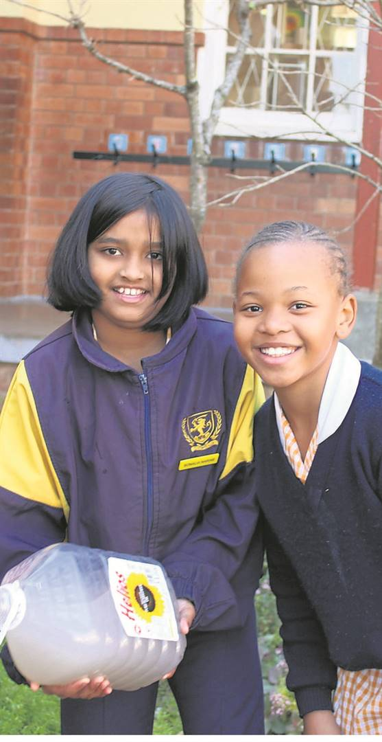 """Scottsville School pupils were challenged to bring """"grey water"""" to school to help keep their gardens green and alive. A total of 1 654 litres were collected, and our gardens look lovely! Well done, boys and girls! Proud to contribute are Sonalia Narine (left) and Philasande Mncube.PHOTO: supplied"""