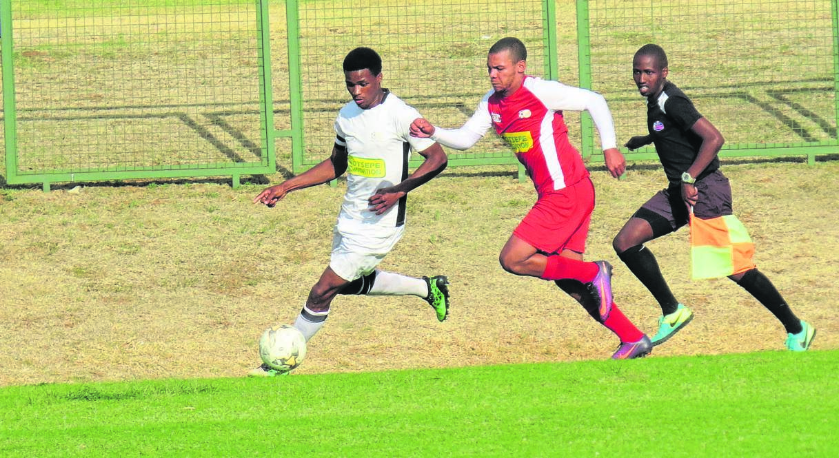 Bloemfontein Young Tigers defender Themba Tonisi and Kovsie forward Ke'anu Baatjies (red) in tight chase for the ball under the watchful eye of assistant referee Michael Fonoza during the team's derby of the ABC Motsepe League played at UFS last Saturday (12/10). Photo: Teboho Setena