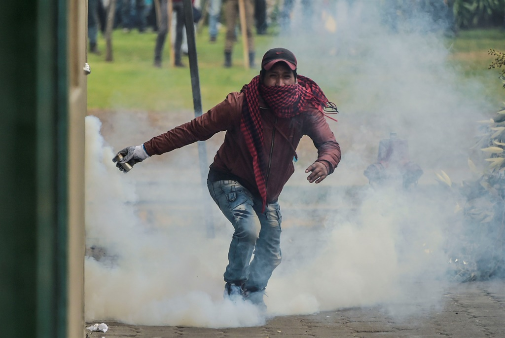 A demonstrator runs holding a tear gas canister during clashes with riot police within a protest over a fuel price hike ordered by the government to secure an IMF loan, in Quito. (AFP)