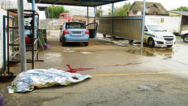A car sits half-cleaned while the body of the woman who was cleaning it before she was stabbed, lies metres away.