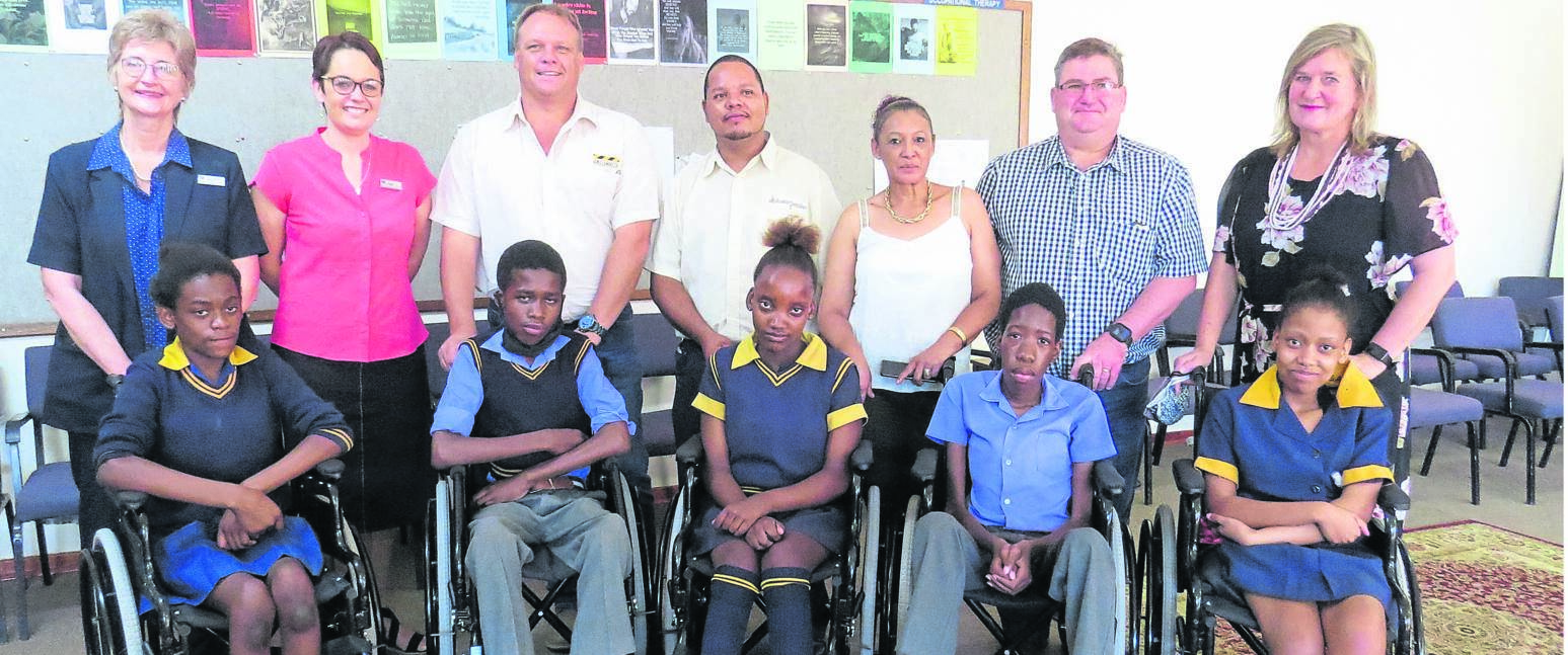 The Tswellang Special School in Bloemfontein received a donation of wheelchairs for learners' use on Thursday (19/11). From the left are, front: Eleanor Pass, Kananelo Raleting, Mathapelo Ndou, Nkosinathi Tau and Lesego Lesala; back: Margueriet Botha (Bloemcare), Nicola Visser (Bloemcare), Gary Lindeque (Mmaki Trading), Dorian Williams (Bloempapier), Lynn Douw (Tau Pele), Christo Labuschagne (Tau Pele) and Verna Vorster (principal of the Tswellang Special School).Photo: Teboho Setena