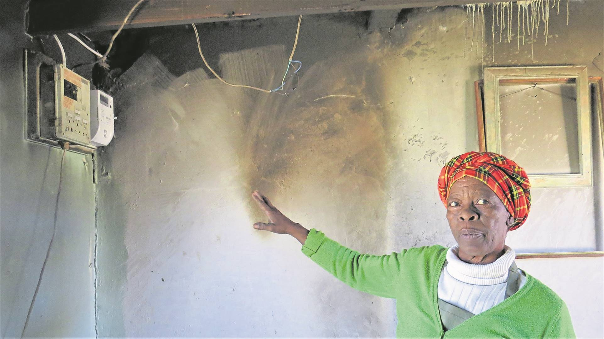 Linah Morake points to the breaker box which exploded in her kitchen.