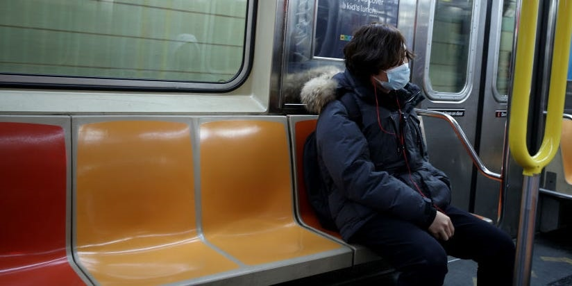 A person riding the New York City subway wears a m