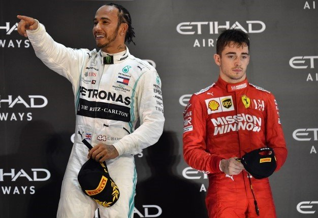 Mercedes' British driver Lewis Hamilton (L, 1st place) and Ferrari's Monegasque driver Charles Leclerc (R, 2nd place), are pictured on the podium at the Yas Marina Circuit in Abu Dhabi, after the final race of the Formula One Grand Prix Formula One Grand Prix season, on December 1, 2019. ANDREJ ISAKOVIC / AFP